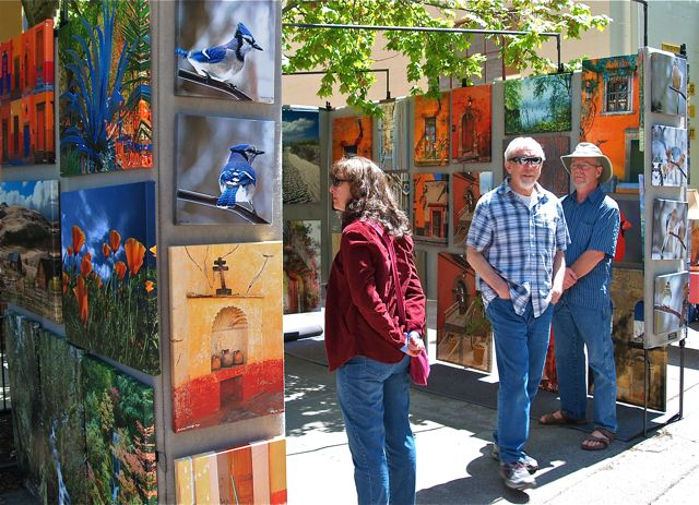Patrons of the arts indulge in beautiful images displayed in the booth of Pat Moore at Lithia Artisans Market.